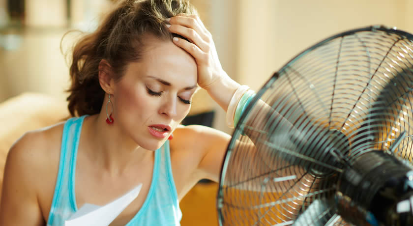 Woman using fan to keep cool in Florida home